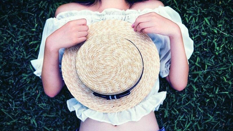 帽子をのせて寝転ぶ女性